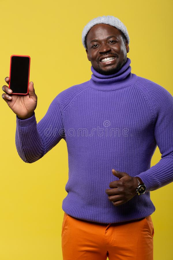 Handsome young man showing his new gadget. Best choice. Pleased dark-skinned male expressing positivity while standing isolated on yellow stock images