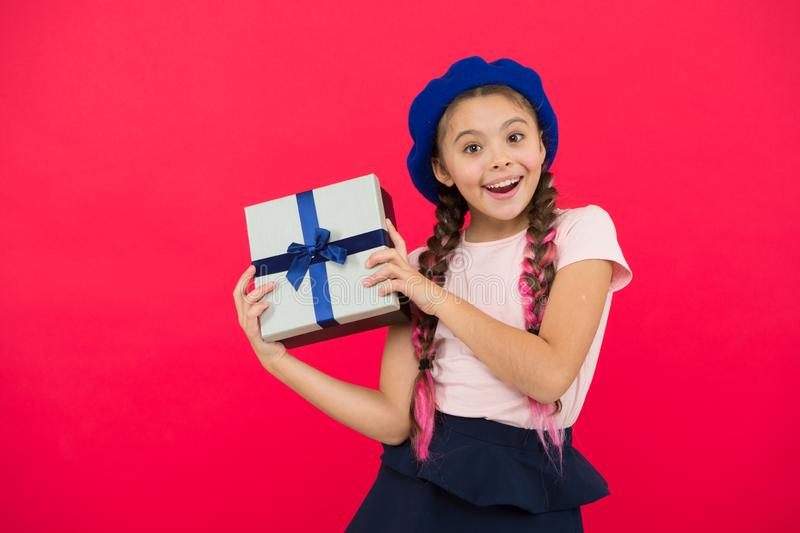 Best christmas gifts. Child excited about unpacking her gift. Kid little girl hold gift box with ribbon on red royalty free stock photo