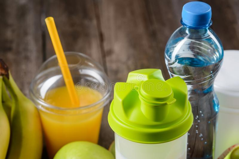 The best drinks for trainings. Consists only of natural ingredients and special sport addition. Special shaker with a protein cocktail, orange juice and mineral stock photo