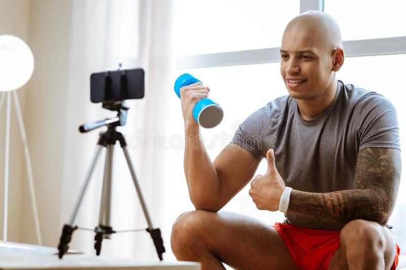Bald bodybuilder recommending best exercises with dumbbells. Best exercises. Bald bodybuilder recommending best exercises with dumbbells for his followers royalty free stock photography