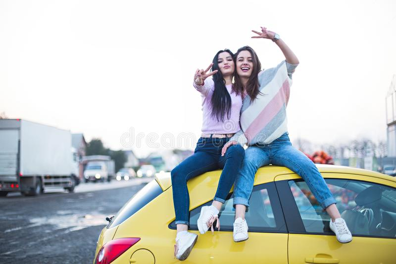 Best female friends cheering by car road trip at sunset. Happy people outdoor on vacation tour stock images