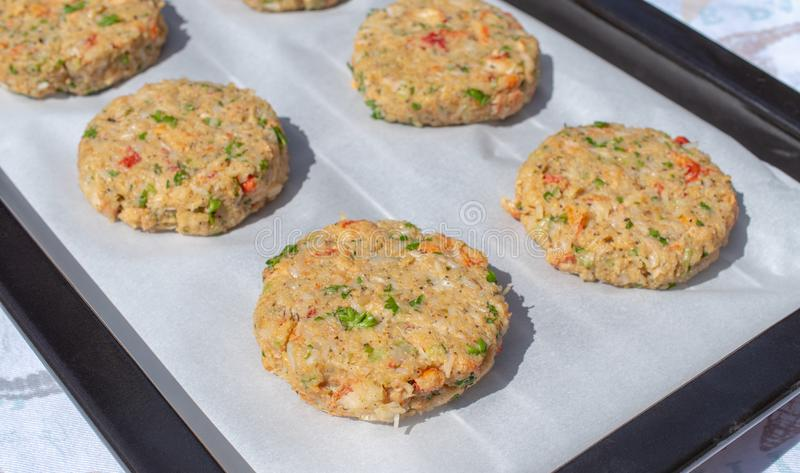 Best fish cakes raw uncooked on  baking tray. .Row of crab patties royalty free stock image