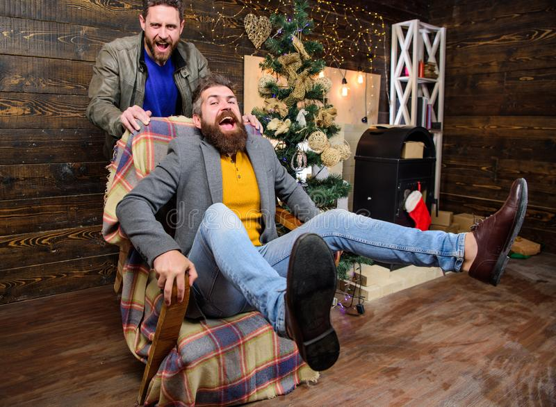 Best friend having fun on christmas eve. Man push armchair with friend. Cheerful men having fun at home. Christmas fun royalty free stock photos