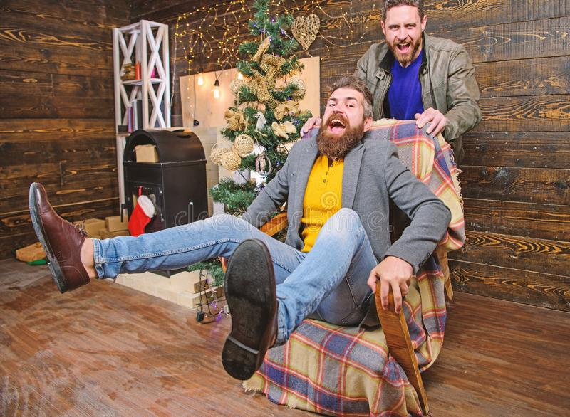 Best friend having fun on christmas eve. Man push armchair with friend. Cheerful men having fun at home. Christmas fun stock images