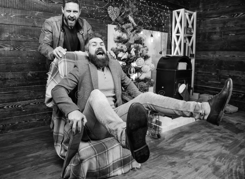 Best friend having fun on christmas eve. Man push armchair with friend. Cheerful men having fun at home. Christmas fun royalty free stock image