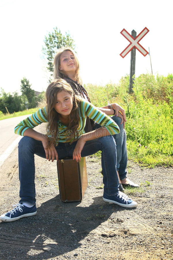 Best friends. Two best friends teenager girls sit on a old luggage with a rail sign in background royalty free stock photo