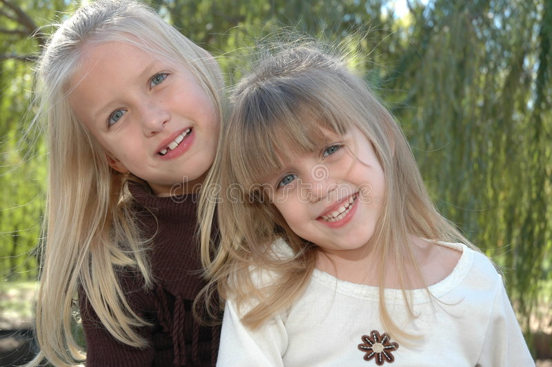 Best Friends. Two beautiful little blond sisters hug each other and laugh. Sisters having a fun time together at the park stock photos