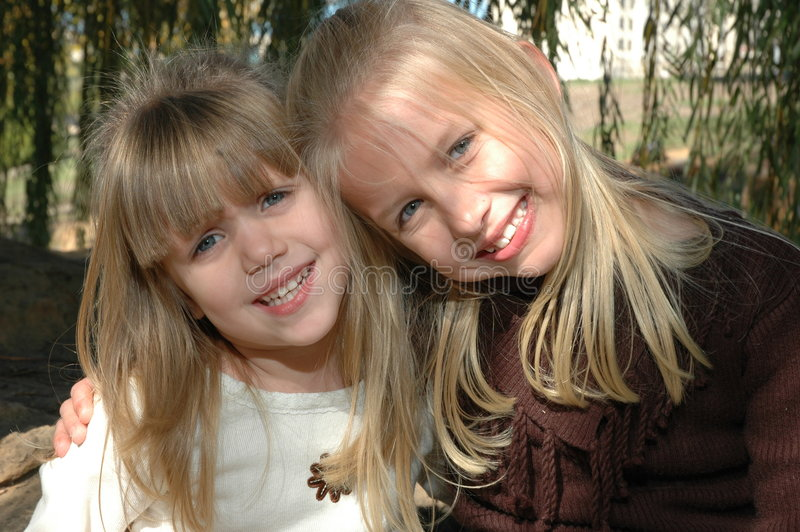 Best Friends. Two beautiful little blond sisters hug each other and laugh. Sisters having a fun time together at the park royalty free stock images