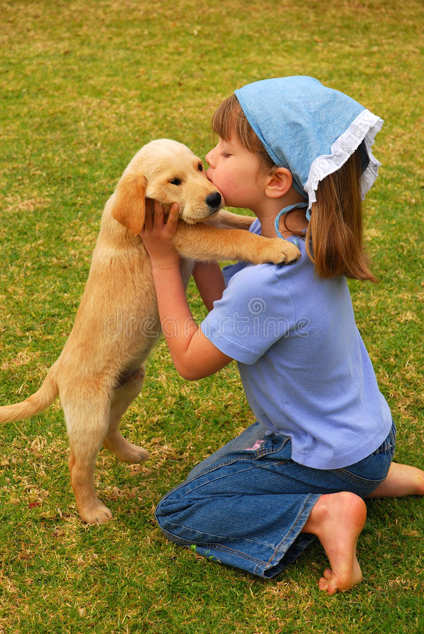 Best friends. A beautiful caucasian little girl child holding and sitting her Labrador Retriever dog puppy with closed eyes in the backyard outdoors