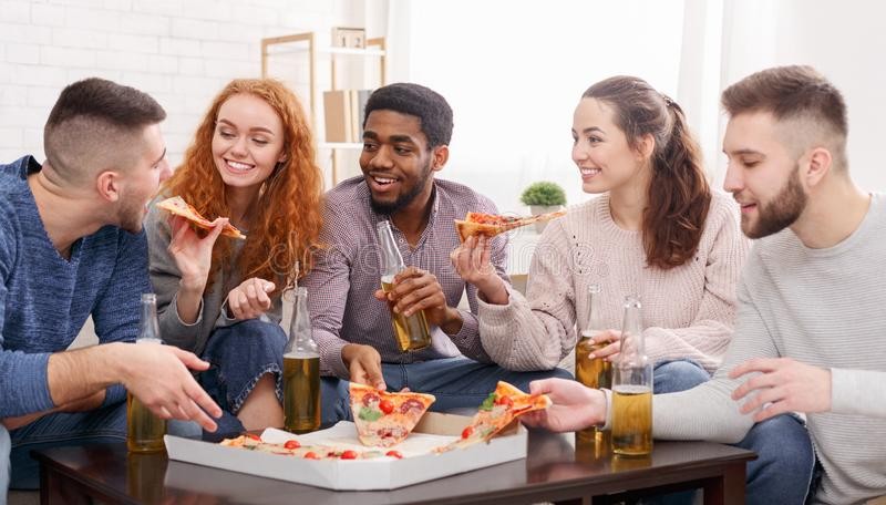 Best friends celebrating meeting, drinking beer and eating pizza royalty free stock photo