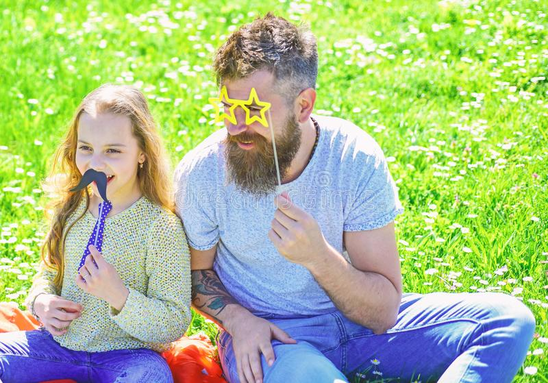 Best friends concept. Dad and daughter sits on grass at grassplot, green background. Child and father posing with. Eyeglases, mustache and tie photo booth royalty free stock images