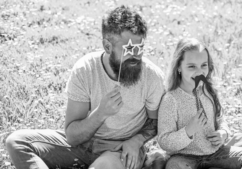 Best friends concept. Dad and daughter sits on grass at grassplot, green background. Child and father posing with. Eyeglases, mustache and tie photo booth royalty free stock photos