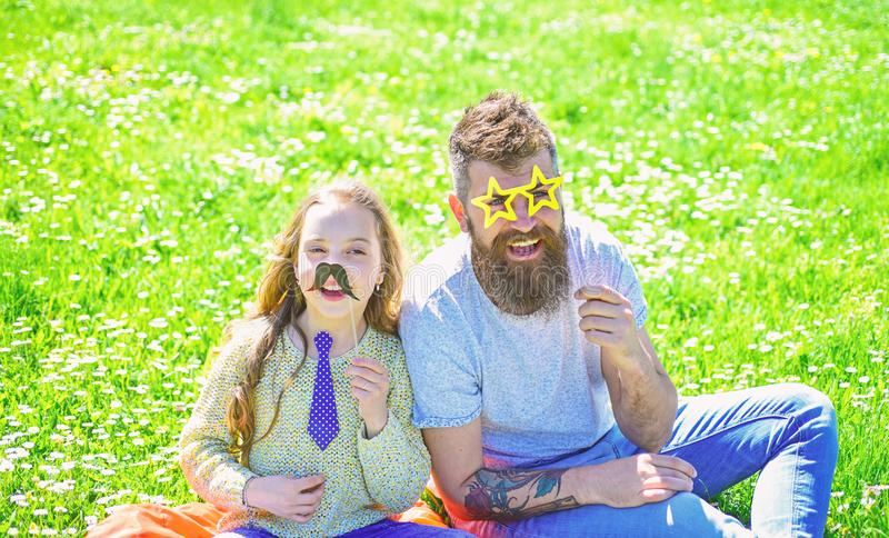 Best friends concept. Dad and daughter sits on grass at grassplot, green background. Family spend leisure outdoors. Child and father posing with eyeglases royalty free stock photos