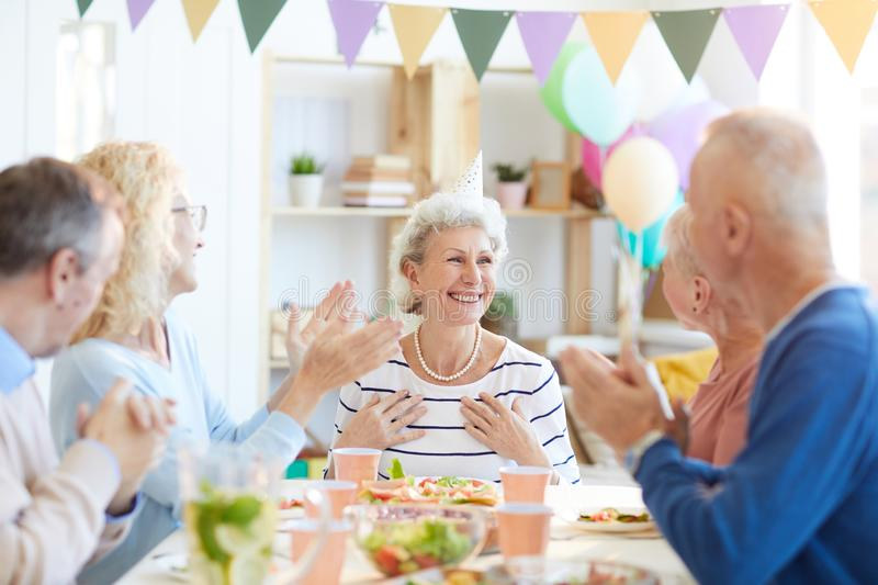 Best friends congratulating retired lady with birthday stock photography