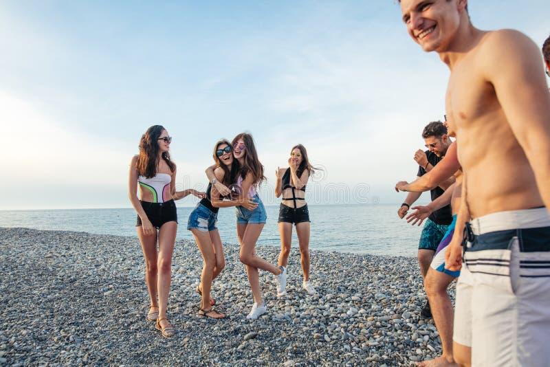Friends dance on beach under sunset sunlight, having fun, happy, enjoy stock photo