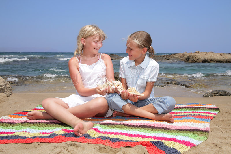Best friends for ever. Two cute girls sitting on a blanket holding seashells stock photography