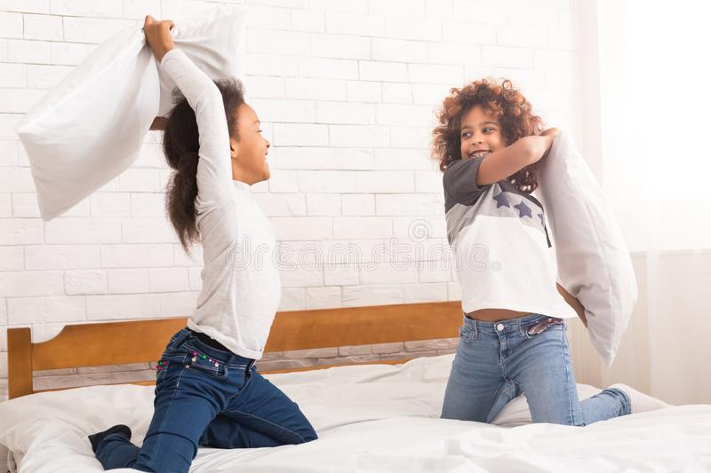 Best friends fighting with pillows, having fun royalty free stock image