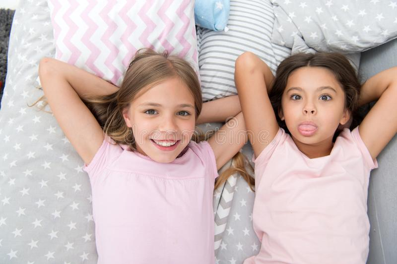 Best friends forever. Girls children lay on bed with cute pillows top view. Pajamas party concept. Girls in playful mood stock photography