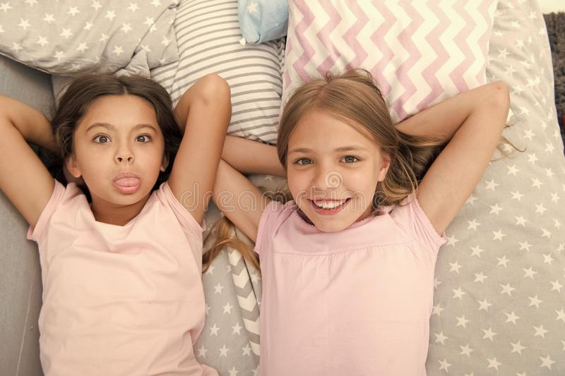 Best friends forever. Girls children lay on bed with cute pillows top view. Pajamas party concept. Girls in playful mood royalty free stock images