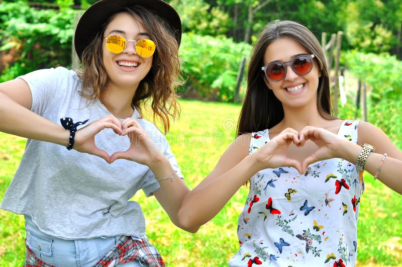 Best friends girls showing heart gesture. royalty free stock images