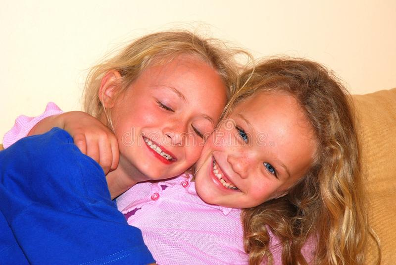 Best friends little girls. Two beautiful cute little Caucasian best friends girls hugging on the couch with happy smiling facial expression stock photography