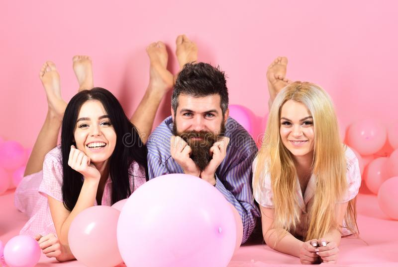 Best friends, lovers near balloons, pink background. Lovers or best friends in pajamas at girlish bedroom party. Gossip royalty free stock photography