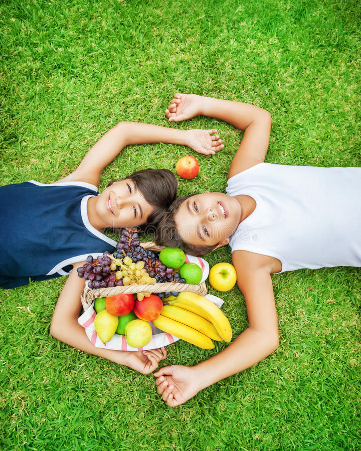 Best friends on a picnic. Two happy teen boys lying down on a fresh green grass field, best friends enjoying picnic outdoors, eating many different tasty fruits royalty free stock images