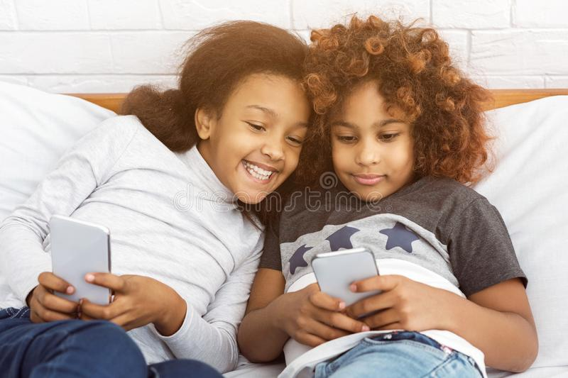 Best friends playing on phones, lying on the bed royalty free stock photography