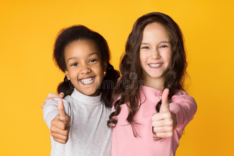 Best friends showing thumbs up on studio background stock photos