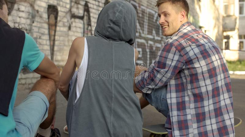Best friends sitting on skateboards and joking, summer holidays, teenagers royalty free stock photos