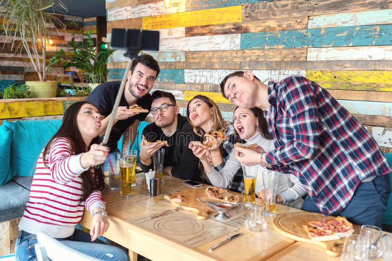 Best friends taking selfie at lunch party with funny faces royalty free stock photos