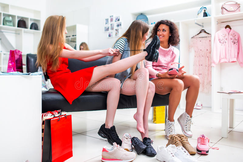 Best friends trying on different shoes talking sitting on a bench in a trendy fashion clothing store royalty free stock photography