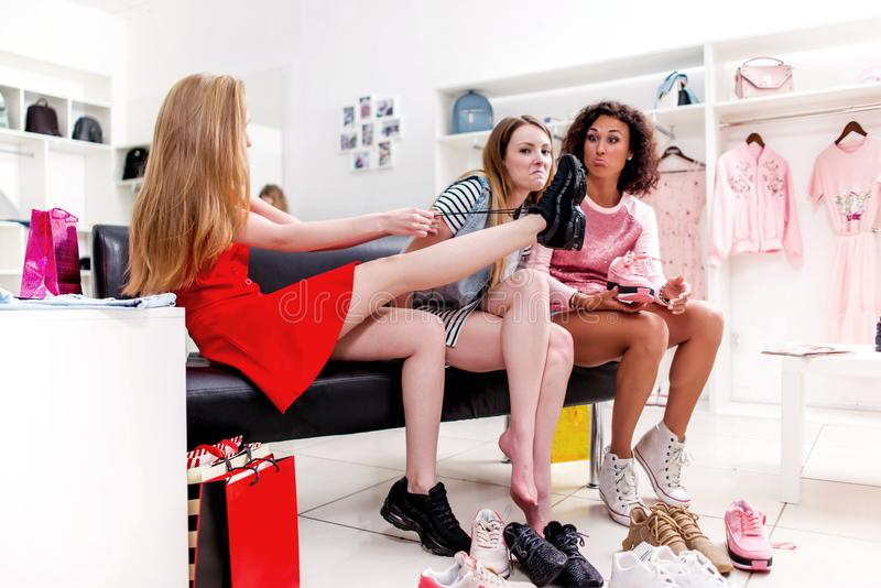 Best friends trying on different shoes talking sitting on a bench in a trendy fashion clothing store.  stock images