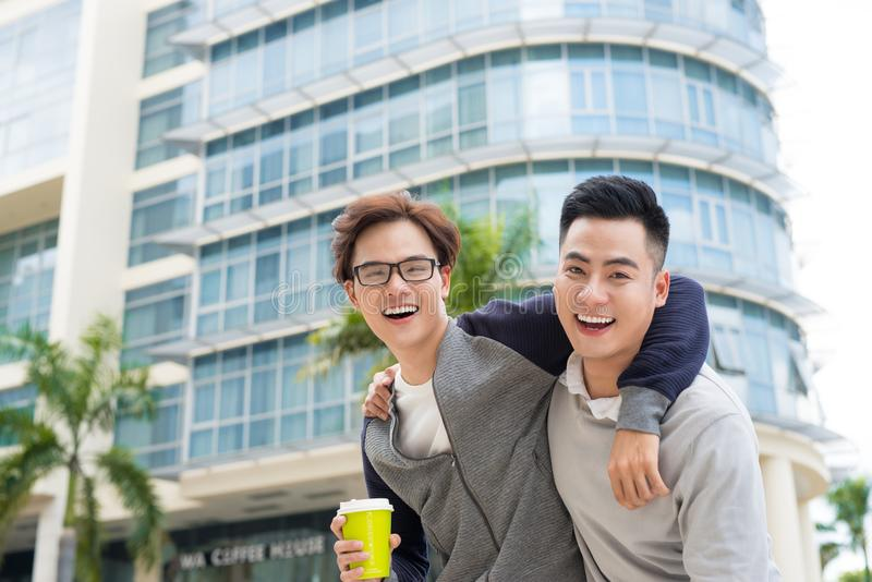 Best friends. Two guys hugging and walking in the city. royalty free stock photography