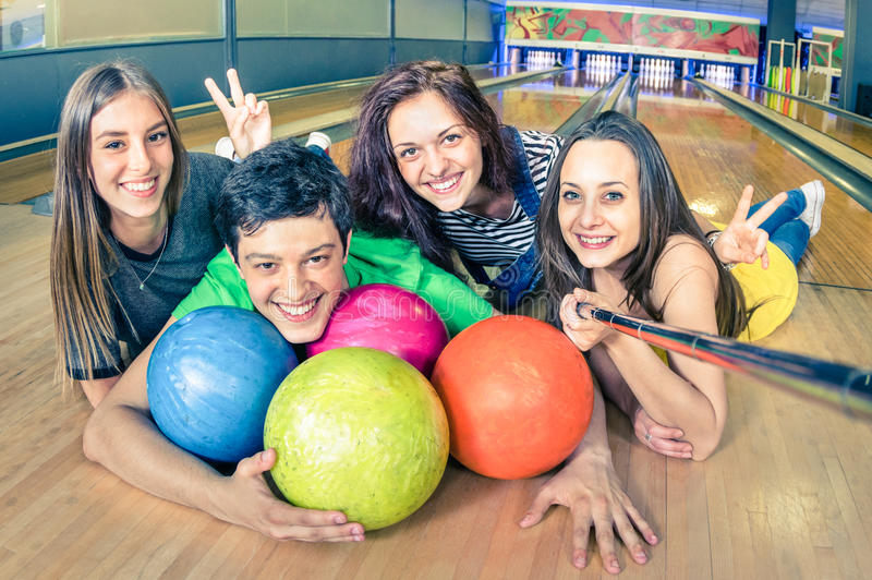 Best friends using selfie stick taking pic on bowling track royalty free stock images