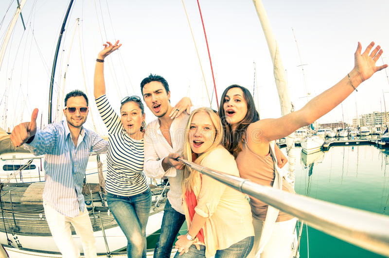 Best friends using selfie stick taking pic on exclusive sailboat. Best friends using selfie stick taking pic on exclusive luxury sailing boat - Concept of royalty free stock photos