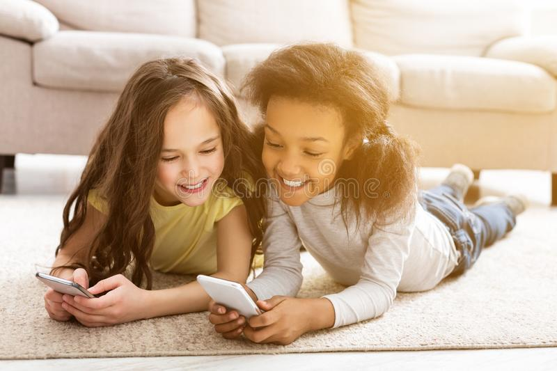 Best friends using smartphones, lying on floor royalty free stock image