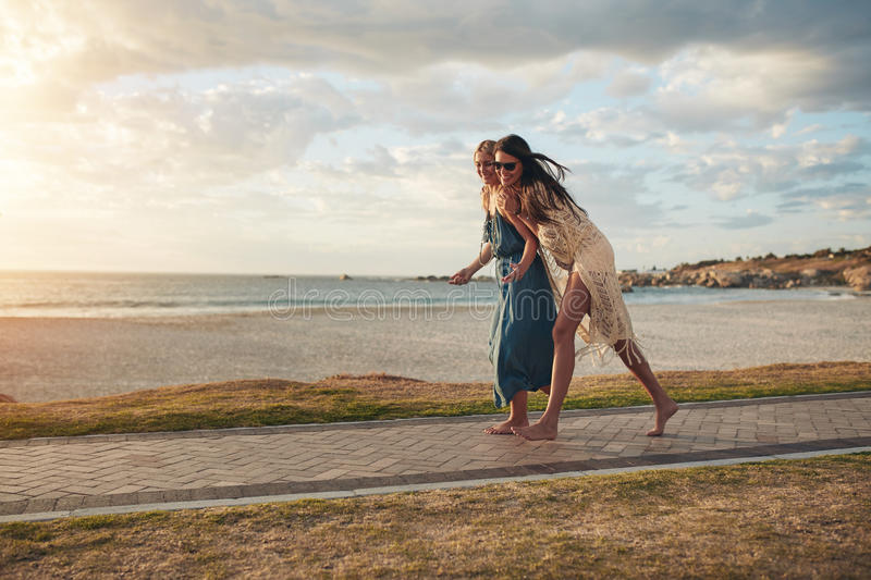 Best friends walking on pathway along a beach royalty free stock photos