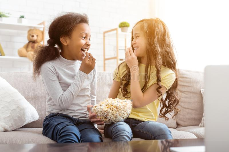 Best friends watching cartoon and eating popcorn royalty free stock photos