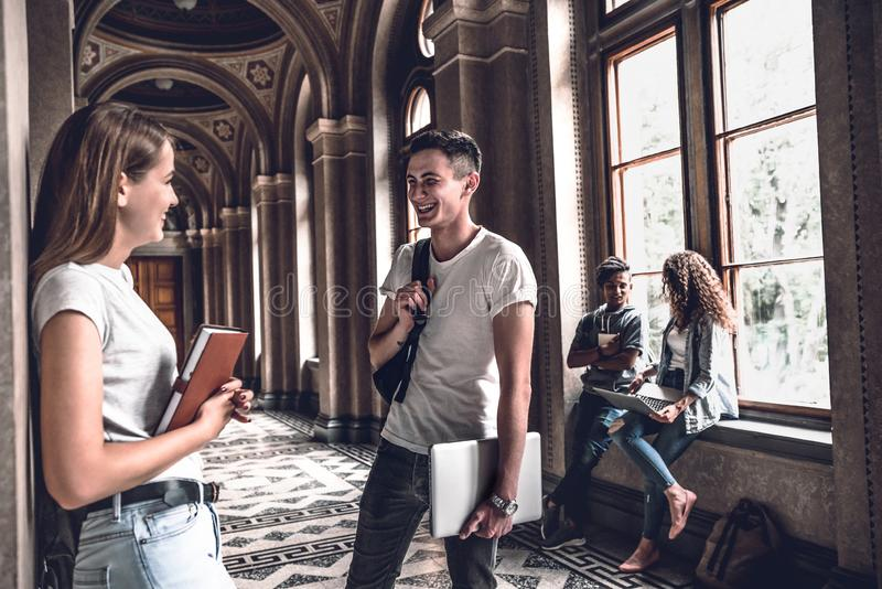 The best friends.Young smiling students standing in the university hall and speak with each other stock photos