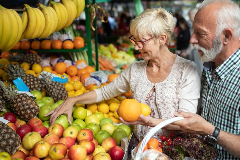 Only the best fruits and vegetables. Beautiful senior couple buying fresh food on market stock photos
