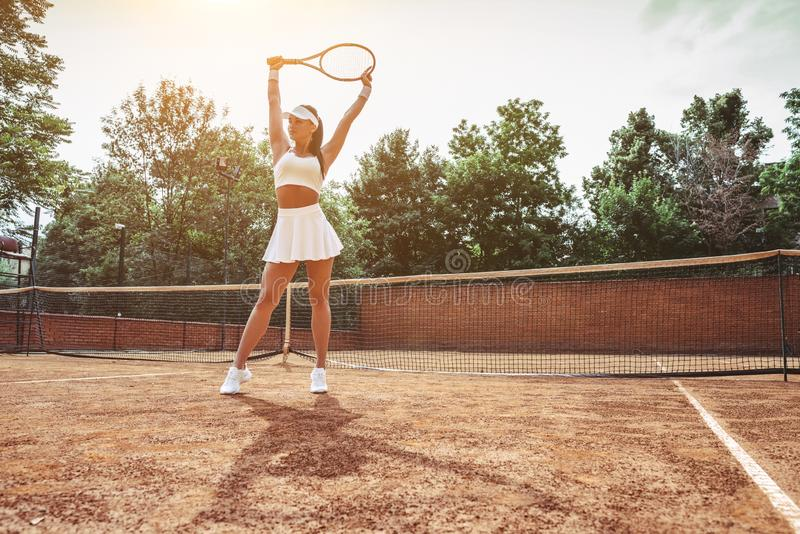 She is the best! Full length of beautiful young woman in sports clothing standing on tennis court. Sporty attractive woman holding stock image