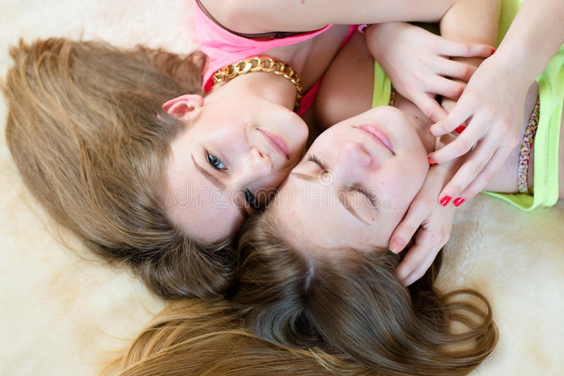 2 best girl friends or sisters beautiful blond young women having fun in bed happy smiling one girl with eyes closed royalty free stock photos