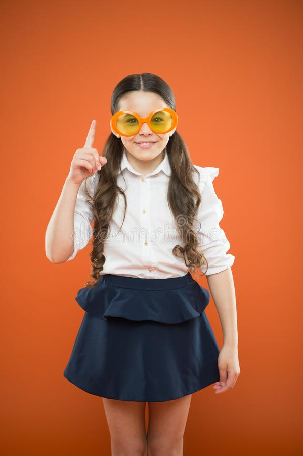 The best glasses for her face shape. Small girl wearing fancy glasses on orange background. Funny child in sun glasses. Pointing up with idea. Little kid stock photo