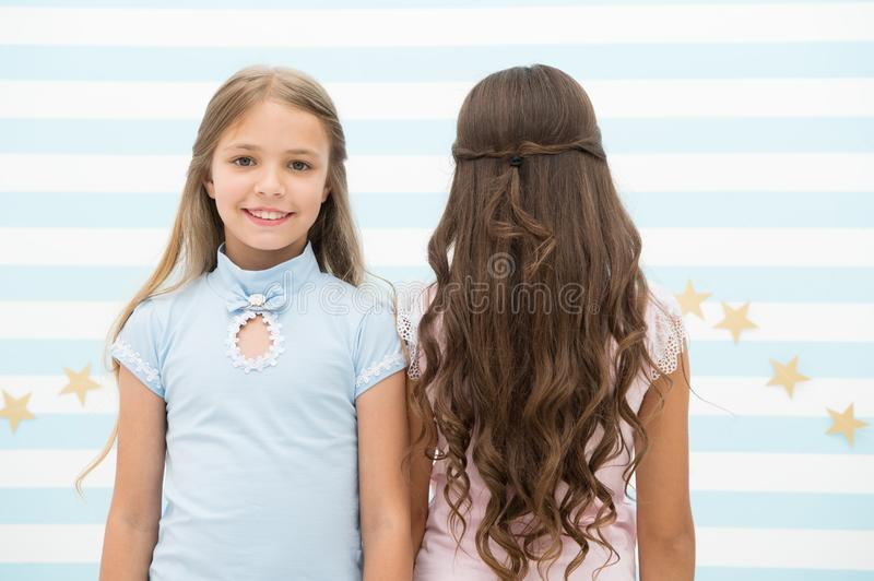 Best hairstyles for long hair. Cute small girls with long brunette and blond curls in playroom. Adorable little children stock photography
