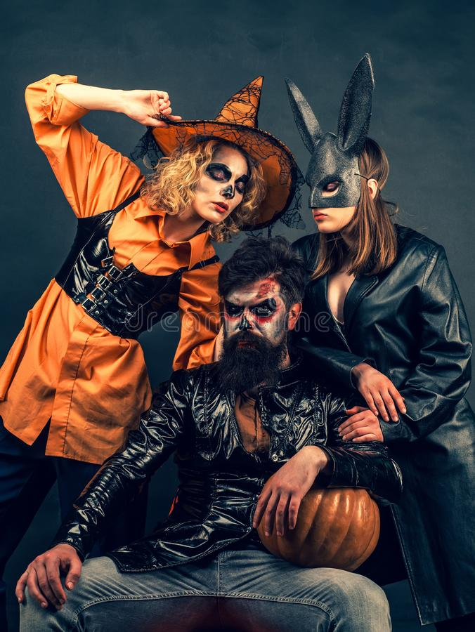Best ideas for Halloween. Group posing with Pumpkin. Fashion Glamour Halloween. Portrait of happy young group in royalty free stock photos