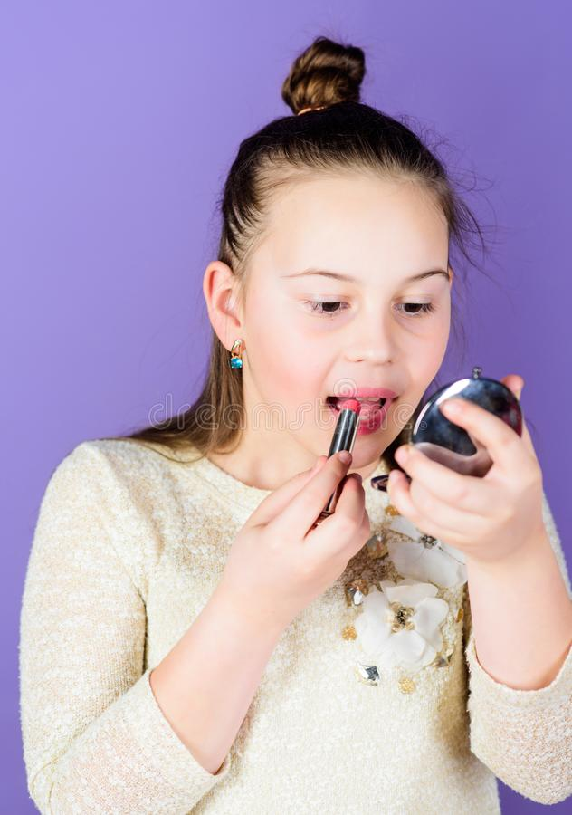 The best lip care treatment. Cute little child applying lip care stick. Adorable girl taking care of her lips. Small. Beauty model being busy with essential lip stock photos