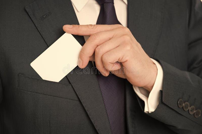 Best?llnings- debiteringkortdesign Den manliga handen satte det tomma vita kortet f?r plast- f?r att stoppa i fickan det klassisk arkivfoton