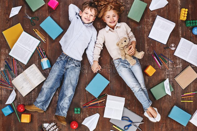Best moments. Children lying near books and toys, holding hands, looking at camera and smiling royalty free stock photography