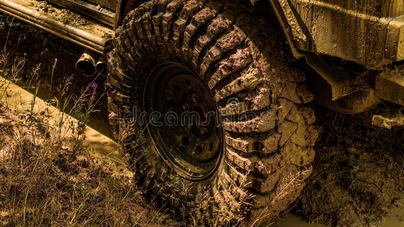 Best Off Road Vehicles. Off-road vehicle goes on the mountain. Bottom view to big offroad car wheel on country road and. Mountains backdrop. Road adventure stock photography